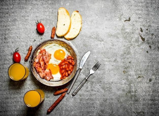 Frühstück am morgen. speck, spiegeleier mit bohnen und orangensaft. auf dem steintisch.
