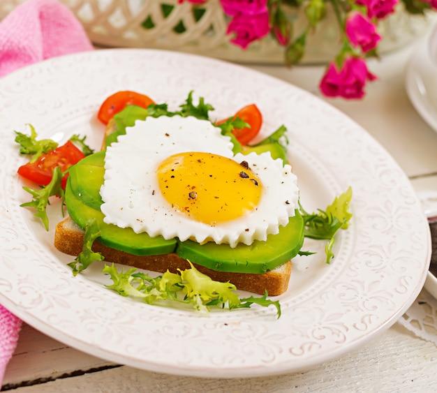Frühstück am valentinstag - sandwich mit spiegelei in form eines herzens, einer avocado und eines frischgemüses. tasse kaffee. englisches frühstück.