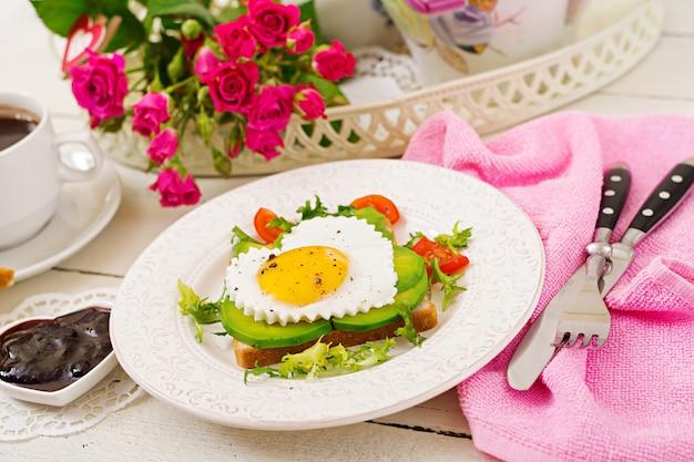Frühstück am valentinstag - sandwich von spiegelei in form eines herzens, avocado