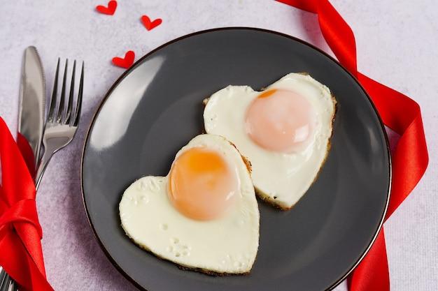 Frühstück am valentinstag - spiegeleier auf teller und rote herzen auf grauem steinhintergrund