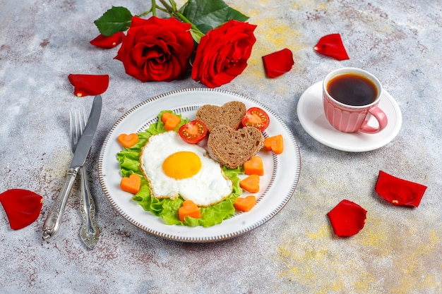 Frühstück am valentinstag - spiegeleier und brot in herzform und frisches gemüse.