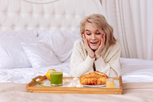 Frühstück anschauen. junge freundin, die sich aufgeregt und glücklich fühlt, wenn sie ein tablett mit frühstück im bett betrachtet