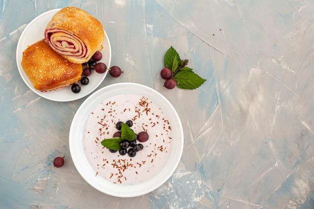 Frühstück auf blauem betonhintergrund. ein teller joghurt mit johannisbeeren und stachelbeeren und ein frisches brötchen mit fruchtfüllung. draufsicht. speicherplatz kopieren.