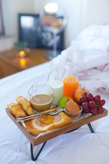 Frühstück auf dem bett mit kaffee, croissants window light