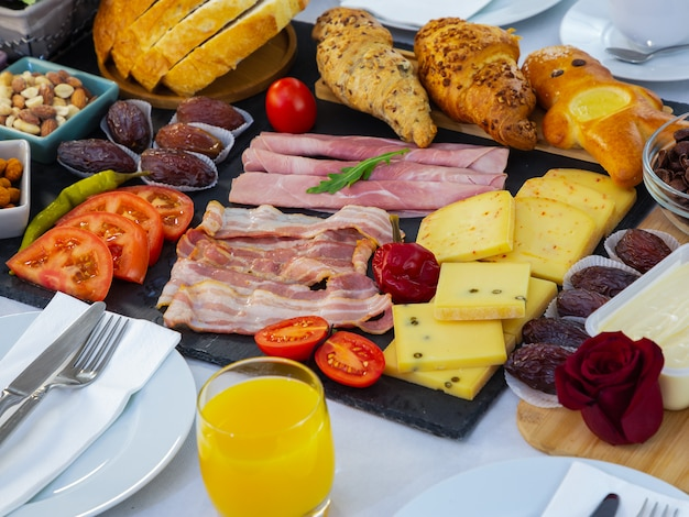 Frühstück auf dem tisch. croissantbrot, croissant müsli, speck, schinken, käse, salat, bohnen, cornflakes, obst, kaffee, tee und orangensaft sind frühstück. , mittag- oder abendessen für jeden tag