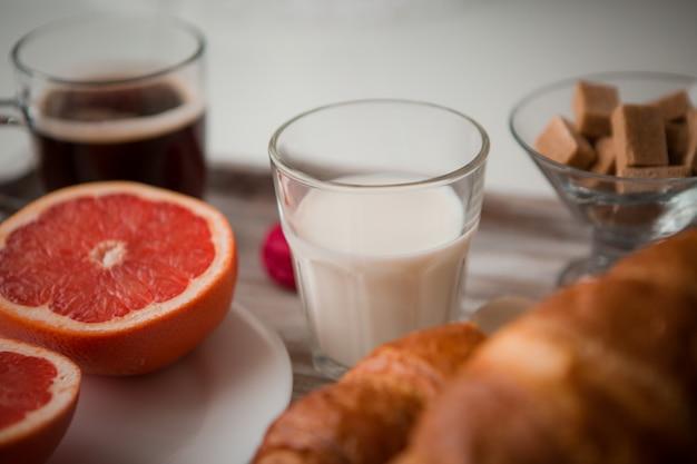Frühstück auf einem tablett - kaffee, croissant, frischer saft