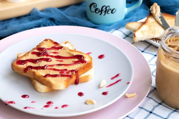 Frühstück auf einem teller toast mit erdnussbutter und beerenmarmelade toaster brot frisches sandwich
