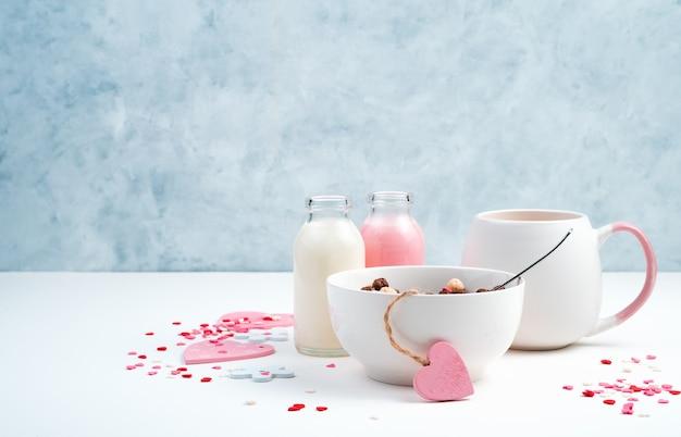 Frühstück auf romantischem hintergrund. müsli in einer weißen tasse, kaffee mit milch und herzen auf einem blauen und