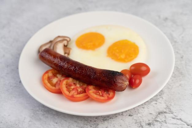Frühstück bestehend aus brot, spiegeleiern, tomaten, chinesischer wurst und pilzen.