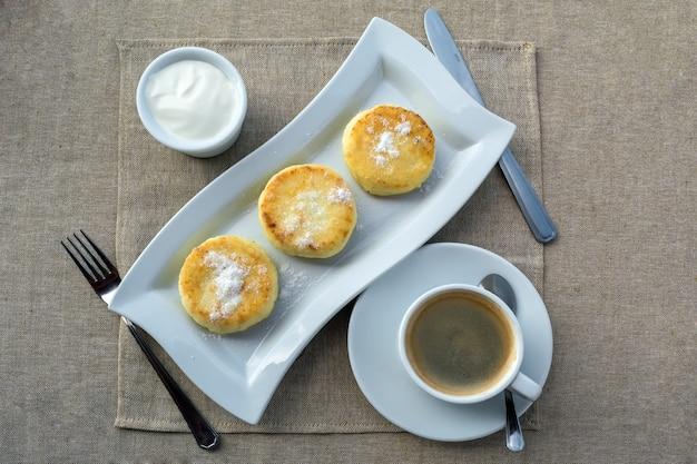 Frühstück bestehend aus pfannkuchen mit sauerrahm und kaffee