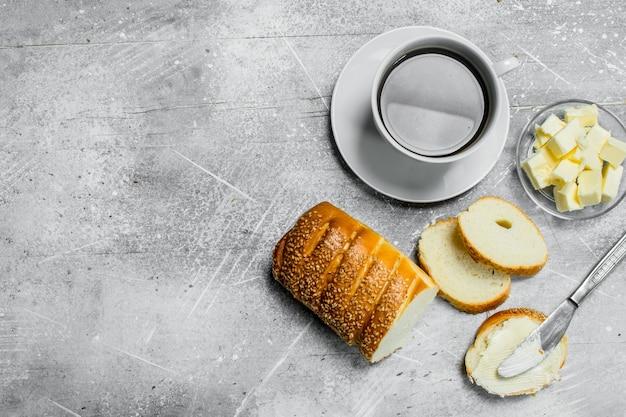 Frühstück. brot mit butter und heißem kaffee. auf einem rustikalen tisch.