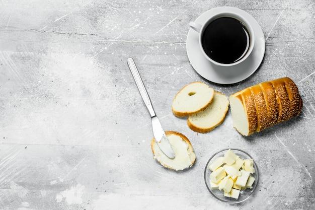 Frühstück. brot mit butter und heißem kaffee auf rustikalem tisch