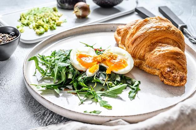 Frühstück, brunch mit avocado, rucola, croissant und ei
