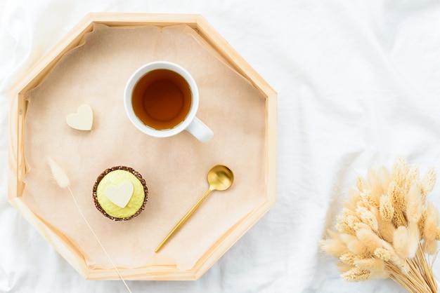 Frühstück cashewkuchen mit einer tasse tee auf einem tablett mit getrockneten blumen