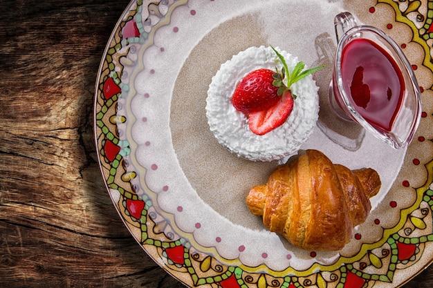 Frühstück. croissant mit quark, erdbeeren und marmelade, auf einem farbteller, auf einem holzbrett. draufsicht
