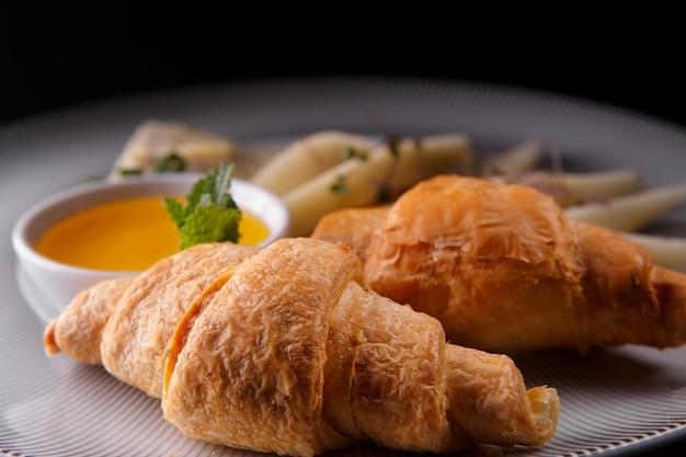 Frühstück. croissants, birne, honig, käse, auf einem weißen teller