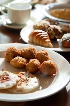 Frühstück, das aus hörnchen-, brötchen-, bonbon-, donut- und bananenbällen auf weißen platten besteht