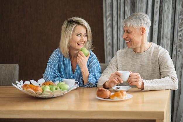 Frühstück des erwachsenen liebespaares zu hause. reifer ehemann und ehefrau sitzen in der küche, glückliche familie, mann und frau trinken kaffee am tisch mit früchten