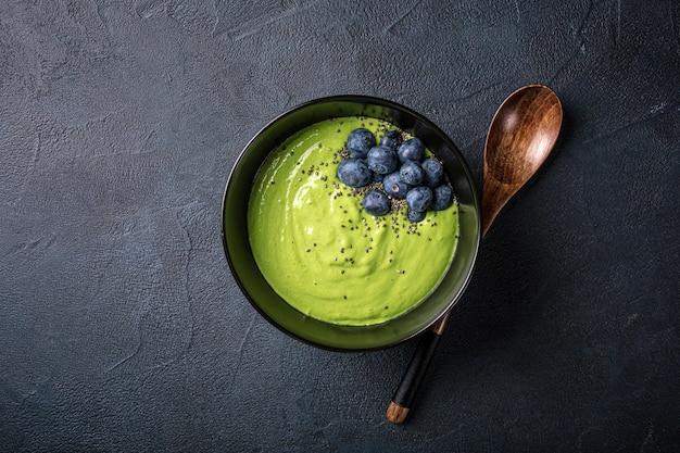 Frühstück detox grüne smoothie schüssel aus banane und spinat auf schwarzer oberfläche