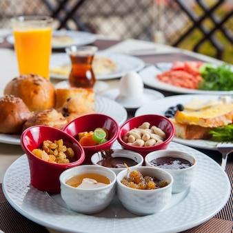 Frühstück draußen mit nüssen, getrockneten früchten, honig, orangensaft, tee seitenansicht