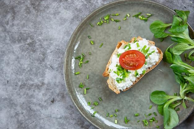 Frühstück. ein stück brot mit quark mit frühlingszwiebeln und tomaten bestrichen