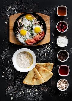 Frühstück essen konzept. pfanne mit eiern, gemüse, haferflocken, pfannkuchen und saucen