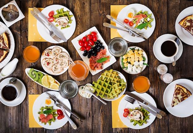 Frühstück essen tisch. festliches brunch-set, abwechslungsreiche mahlzeit mit spinatwaffeln, lachs, käse, oliven, hähnchenröllchen und käsekuchen. ansicht von oben. flach liegen