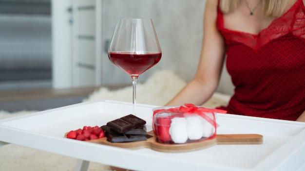 Frühstück für freundin. valentinstag morgen. wein und süßigkeiten auf einem weißen tablett. frühstück im bett. mädchen in einem roten peignoir im hintergrund