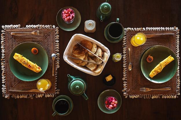 Frühstück für zwei - omelett, obst, pfannkuchen und kaffee auf dem holztisch