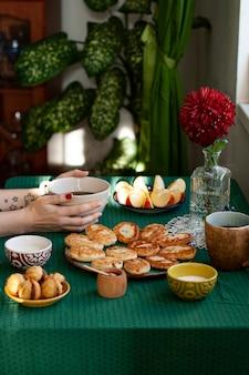 Frühstück für zwei personen: käse mit rosinen aus hausgemachtem käse, sauerrahm, schwarzem kaffee, apfel und nüssen mit kondensmilch. auf dem tisch steht eine transparente vase mit roter chrysantheme.