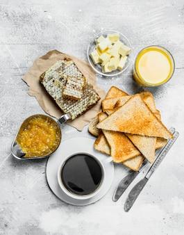 Frühstück. geröstetes brot mit butter, honig und orangenmarmelade auf rustikalem tisch
