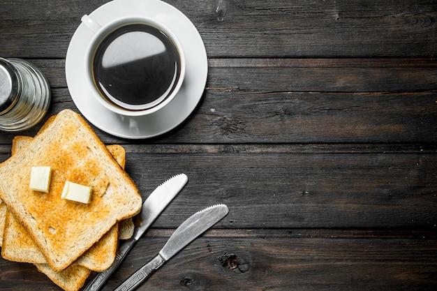 Frühstück. geröstetes brot mit butter und aromatischem kaffee. auf einem hölzernen hintergrund.