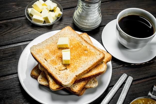 Frühstück. geröstetes brot mit butter und aromatischem kaffee. auf einer holzoberfläche.