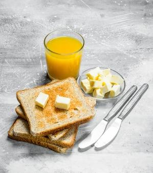 Frühstück. geröstetes brot mit butter und einem glas orangensaft. auf einem rustikalen tisch.