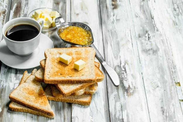 Frühstück. geröstetes brot mit butter und heißem kaffee. auf rustikaler holzoberfläche.