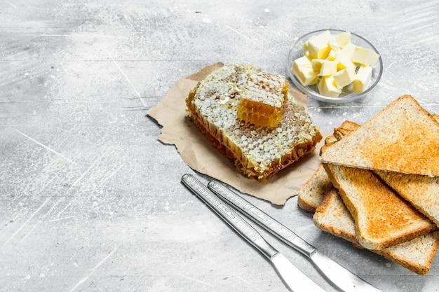 Frühstück. geröstetes brot mit butter und honig. auf einem rustikalen.