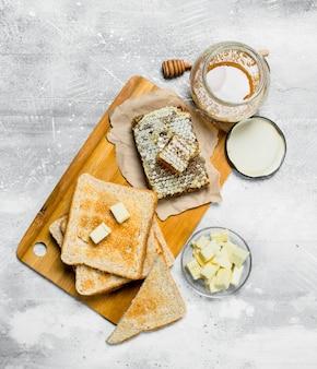 Frühstück. geröstetes brot mit butter und honig. auf einer rustikalen oberfläche.