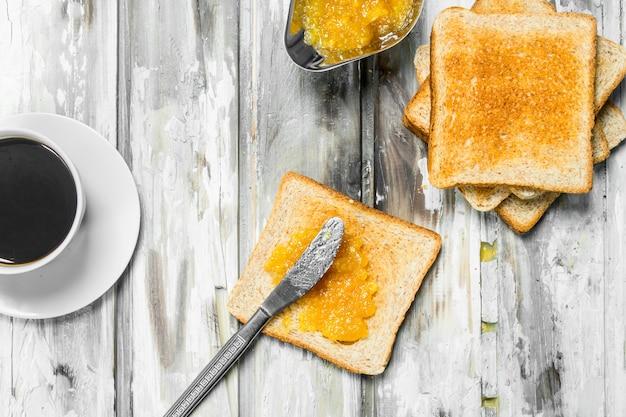 Frühstück. geröstetes brot mit orangenmarmelade. auf rustikalem holztisch.