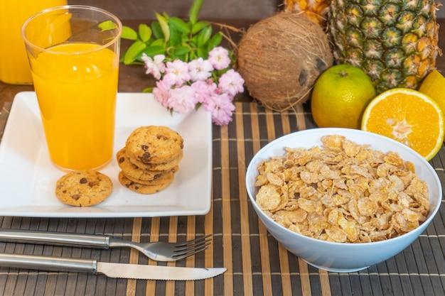 Frühstück gießt milch in cornflakes, die spritzenapfel und orange frucht schaffen