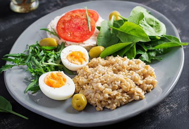 Frühstück haferbrei mit gekochtem ei, tomatensandwich, rucola und spinat. gesundes essen.
