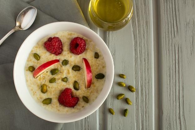 Frühstück: haferflocken mit apfel, himbeeren, honig und nüssen auf dem grauen hölzernen hintergrund. draufsicht.