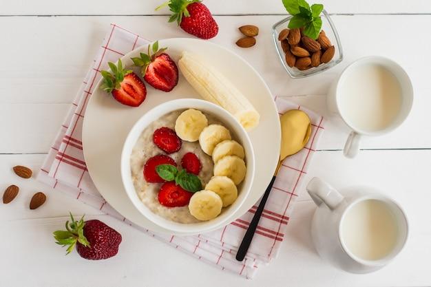 Frühstück. haferflocken mit bananen, erdbeeren, nüssen auf dem holzbakground. gesundes frühstück. nahaufnahme. ansicht von oben.