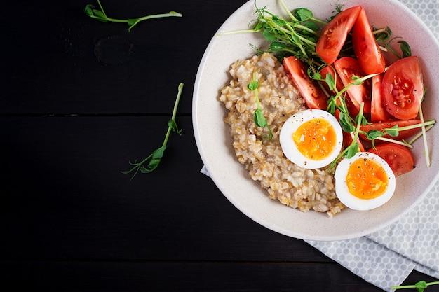 Frühstück haferflockenbrei mit gekochtem ei, kirschtomaten und microgreens