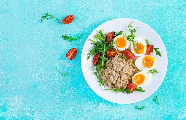 Frühstück haferflockenbrei mit gekochtem ei, kirschtomaten und rucola