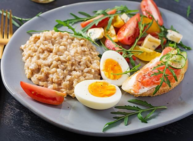 Frühstück haferflockenbrei mit gekochtem ei, lachssandwich und tomatensalat. gesundes essen.