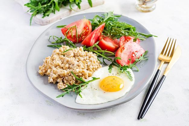 Frühstück haferflockenbrei mit spiegelei, tomaten, rucola. gesundes essen.