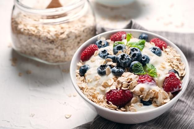 Frühstück, hafermehl mit blaubeere und himbeere auf weißer schüssel morgens.
