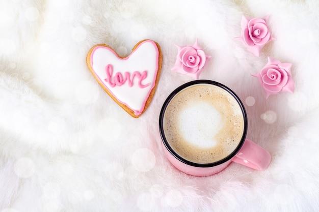 Frühstück im bett am valentinstag mit kaffee und herzförmigem keks in der nähe von blumen