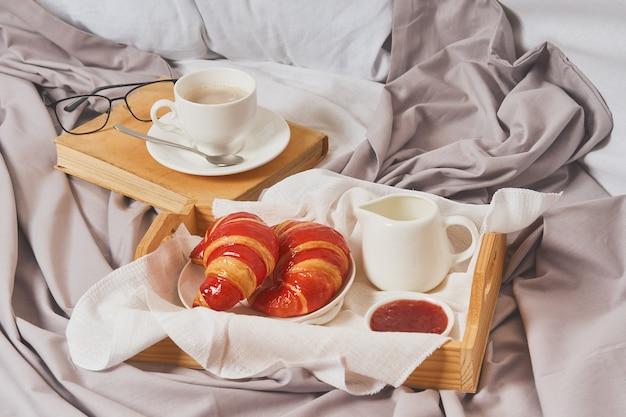 Frühstück im bett, kaffee mit sahne, croissants in marmelade