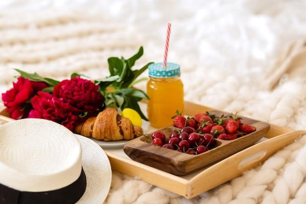 Frühstück im bett mit kaffee, croissants, erdbeeren und saft
